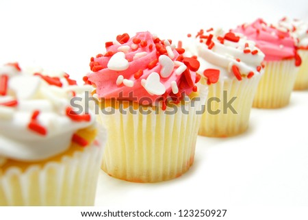 Row of pink and white Valentines Day cupcakes with sprinkles over white