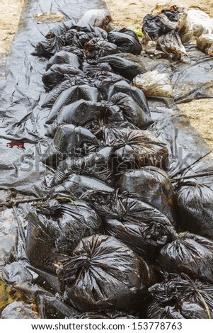 Row of Plastic bags which contain crude oil from the clean up operation on oil spill accident on Ao Prao Beach at Samet island on July 2013 in Rayong, Thailand.