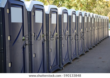 Row of portable toilets on a city street #590133848