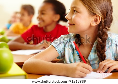 Row of pupils looking at teacher with cute girl in front