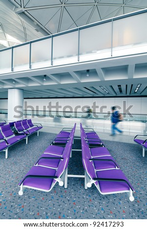 row of purple chair at airport with moving traveler , blue tone