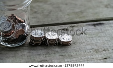 Row of Quarters stacked up next to a jar half full of coins on old wooden floor board. Finance and Investing strategy concept.