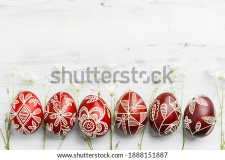 Row of red and white handmade wax dyed Easter eggs. Ukrainian pysanka frame on white wooden background with copy space for text Foto d'archivio ©