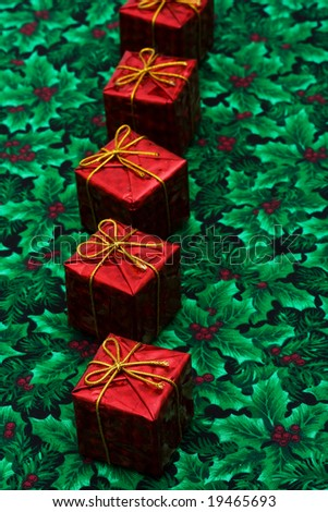 Row of red Christmas presents on leaf and holly berry background, Christmas presents