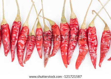 row of red peppers on white