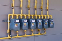 Row of residential natural gas meters and yellow pipe plumbing on exterior wall to measure household energy consumption