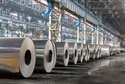 Row of rolls of aluminum lie in production shop of plant.