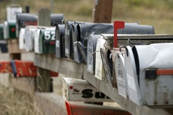 Row of rural mailboxes, one with red flag up indicating mail to be sent.