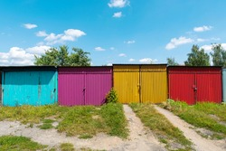 Row of rusty garages or outdoor storage sheds. Old garage door closed with latch, padlock or hasp. Pattern of colorful door