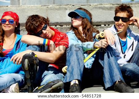 Row of several teens relaxing outside