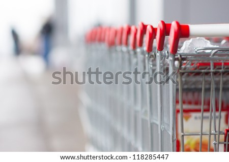 Row of shopping carts near entrance of supermarket