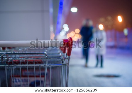Row of shopping carts on winter street at evening near store