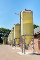 Row of silos with feed at livestock on european farm