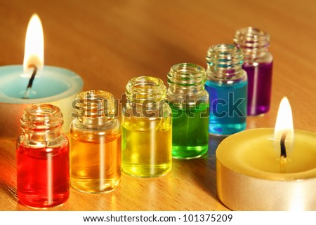 Row of six bottles with colored aroma oils and two candles on table - stock photo