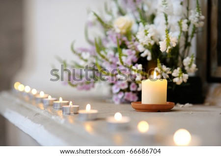 Row of small candles and purple flowers at church