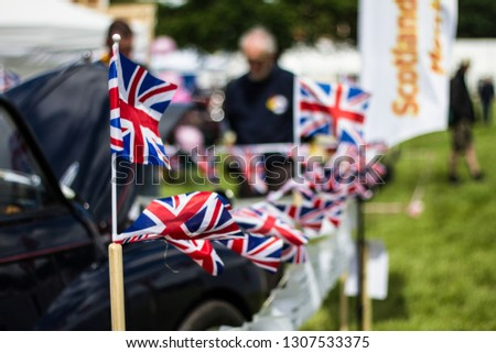 Row of small Union Jack Flags in the breeze at a Car Show Festival.  Classic car to one side and grass to the other. #1307533375