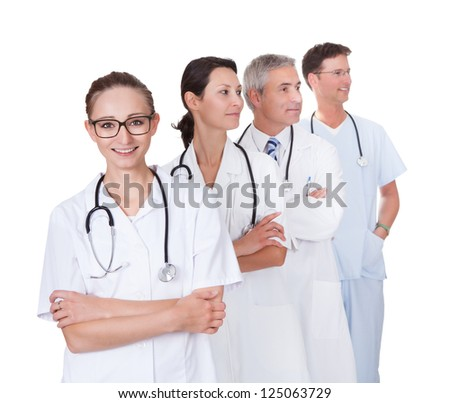 Row of smiling diverse medical doctors and nurses in white uniforms with stethoscopes standing in an oblique receding row isolated on white