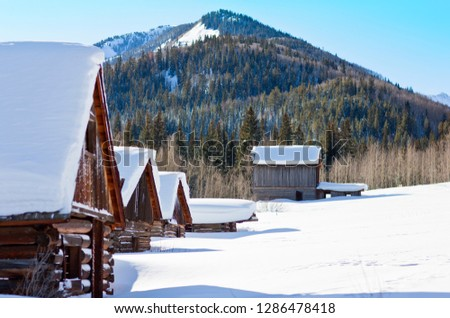 Row of snow-covered log cabins in a wintry setting.