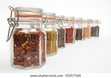 Row of spice jars containing various herbs and spices