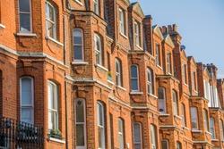 Row of tall upmarket residential red brick buildings in Kensington, London