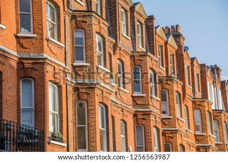 Row of tall upmarket residential red brick buildings in Kensington, London