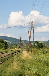 Row of telegraph poles along old railway track. Summer sunny evening time. Division of double-track line to different directions.
