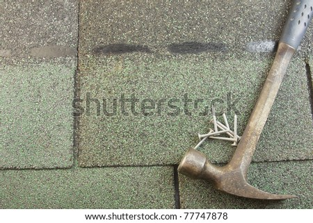 row of textured green asphalt shingles with hammer and roofing nails