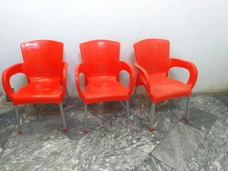 Row of three red plastic chairs on gray marble background. Furniture series. Selective focus.