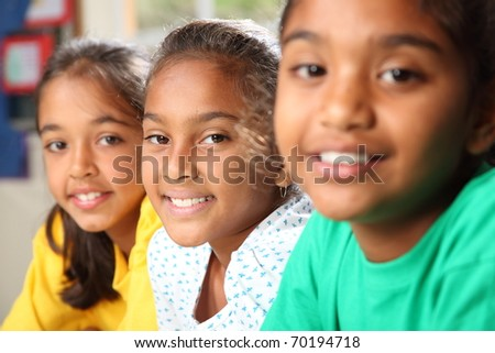 Row of three smiling young school girls sitting in class