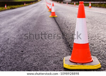 Row of traffic cones along the middle of a road being resurfaced. #1098928898