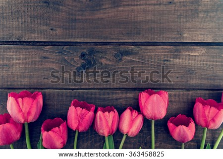 Row of tulips on wooden background with space for message.  Mother\'s Day background. Top view