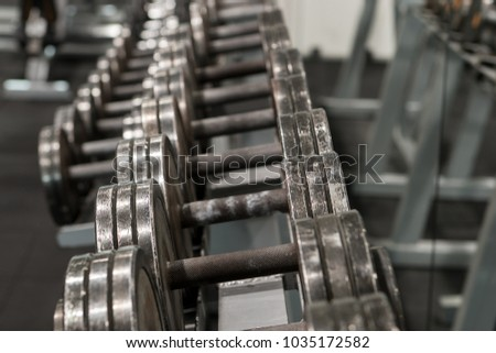 Row of used metal dumbbells on a rack in a gym. Sport and fitness equipment. #1035172582