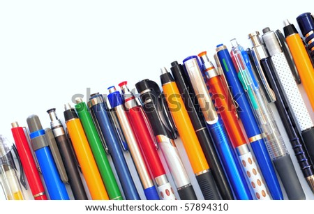 Row of various multicolored ball pens on white background - stock photo