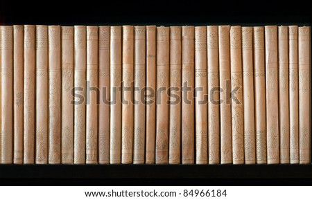 Row of vintage beige dirty books in  bookcase