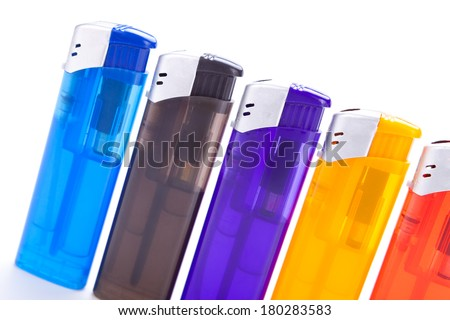 Row of vividly coloured plastic disposable lighters for smokers in red, yellow, two shades of blue and black isolated on a white background