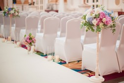 row of wedding chairs decorated with flowers