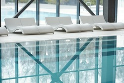 Row of white plastic deckchairs standing along large windows and swimming pool with transparent water inside modern spa center
