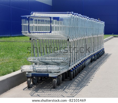 Row of white shopping carts in front of a shopping center