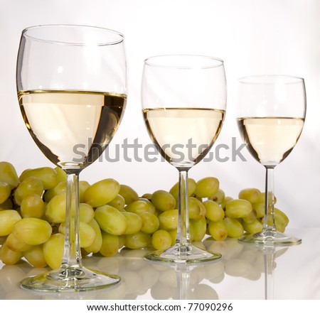 Row of white wine glasses and grapes