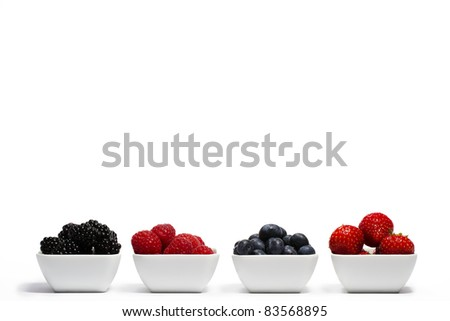 row of wild berries in bowls on white background