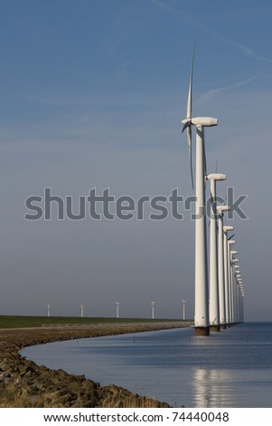 Row of windmills standing in the water