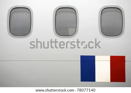 Row of windows of a passenger plane with the flag of France