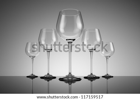 Row of wine glasses on reflective ground