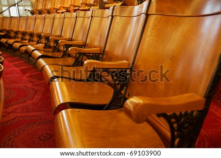 Row of wood and steel folding gallery seats in California State Capital Building with red carpet