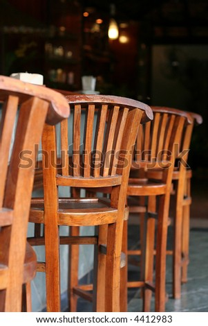 Row of wooden outdoor chairs in tropical style