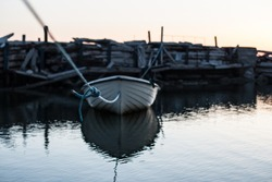 Rowboat attached to a rope in an old deserted harbour