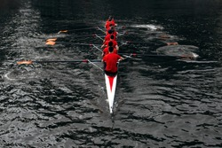 rowers rowing in the dark water. The concept of team sports