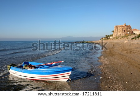 Rowing boat, castle and beach at Sunrise in Marbella Southern Spain