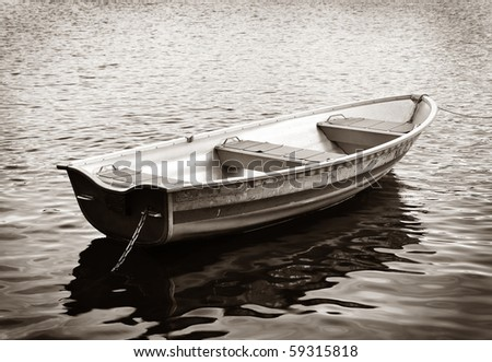 Rowing boat in black and white in calm water.