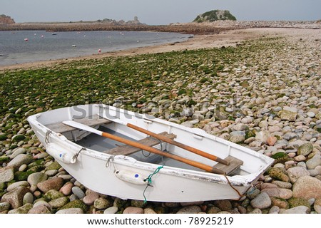 rowing boat on deserted pebble beach in isles of scilly, uk